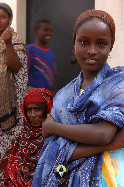 A woman of Alaili Dadda poses for the camera while U.S. military troops ask questions of the village elders. In order to make this picture the photographer befriended a young man who asked the woman if the photographer could make the picture. She agreed, and looked at the camera. This was uncommon.  Djiboutian women are very  shy and deferent to men in most cases. It is considered rude to look at women and speaking to them is also considered inappropriate. <br />