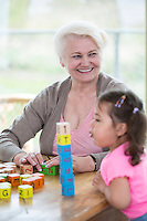 Happy grandmother looking away while granddaughter blowing stacked alphabet blocks in house