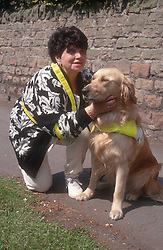 Woman with visual impairment crouching down in street stroking guide dog,