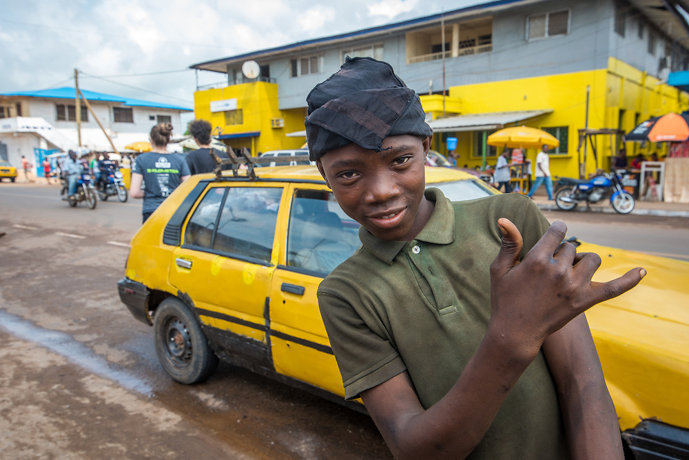 A boy poses for the camera as a yellow car go by in Ganta Liberia