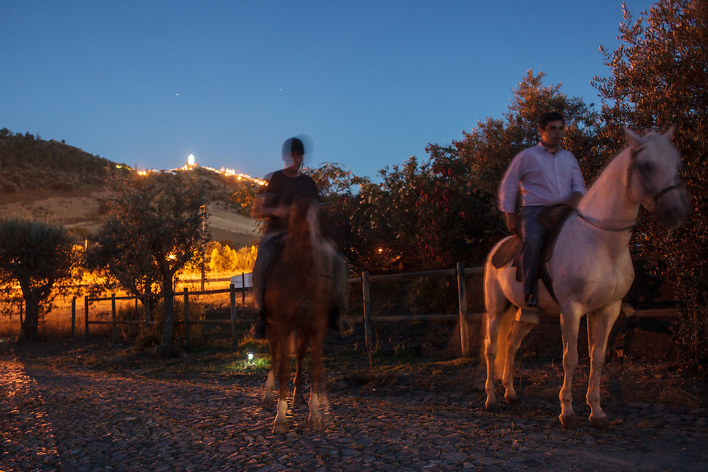 Two men riding horses at night at Casa Saramago in Telheiro village, near Reguengos de Monsaraz in the Alentejo region, Portugal.