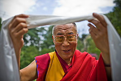 Dalai Lama poses as he receives khata, a white scarf given to honor higher Tibetan Lama  at his residence in Dharamsala, India, May 25, 2009.