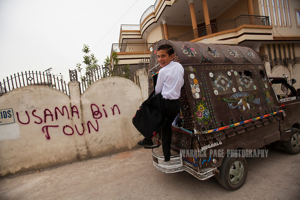 A Pakistani school boy rides on the back of a van to school past recently spray-painted graffiti in Bilal Town, on the road leading to the compound where Osama Bin Laden was killed by US forces, on 6 May, 2011, in Abbottabad, Pakistan. Bin Laden was killed during a U.S. military mission on May 2, at the compound. The Obama administration have decided not to release photographs of Bin Laden's body. (Photo by Warrick Page)