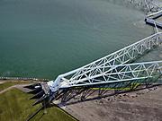 Nederland, Zuid-Holland, Hoek van Holland, 14-09-2019; Nieuwe Waterweg, Haven van Rotterdam. Functioneringssluiting Maeslantkering. De waterkering in de Nieuwe Waterweg wordt een maal per jaar, voordat het stormseizoen begint, getest. Tijdens het sluiten van de kering ligt alle scheepvaartverkeer naar de Rotterdamse haven stil. Details van de constructie, de scharnieren. De Maeslantkering sluit normaal gesproken alleen bij dreigende stromvloed en bij een waterstand van 3 meter of meer boven NAP. De kering, onderdeel van de Deltawerken, vormt samen met de Hartelkering de Europoortkering en beschermt Rotterdam en achterland bij extreme waterstanden.<br /> Hook of Holland - Port of Rotterdam. Aerial view of the new storm surge barrier (Maeslantkering) in the Nieuwe Waterweg during the so-called functioning closure, taking place one a year before the storm season begins. The waterway, leading to the Port of Rotterdam (at the horizon), is closed during the test. <br /> luchtfoto (toeslag op standard tarieven);<br /> aerial photo (additional fee required);<br /> copyright foto/photo Siebe Swart