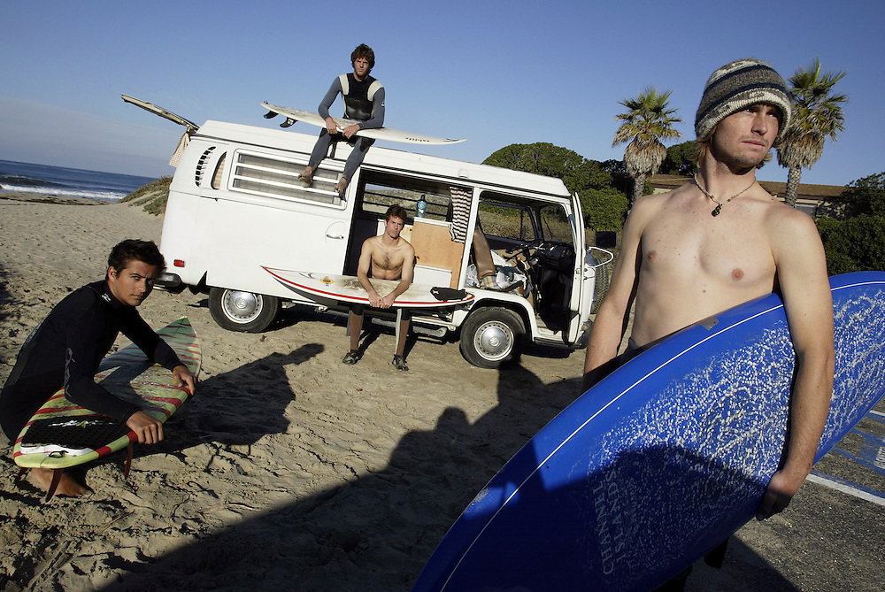 Mike Kalish ( black Xcel wetsuit), twin brother  Charlie Kalish (brown wetsuit), Joe Turpel (red and yellow board,) Aaron Gilliam (wool hat) pose in front Gilliam's VW van at a beach north of Santa Barbara, CA