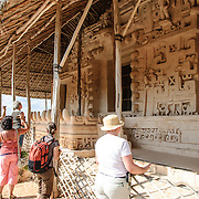 """Tourists admire the carved decorations on the exterior of the Tomb of Ukit Kan Le'k Tok' on top of the Acropolis on the northern side of the Ek'Balam archeological site on Mexico's Yucatan Peninsula. It was once a thriving city of Maya Civilization dating to the Late Classic period. It is 30km north of Valladolid and is named for """"Black Jaguar"""" a distinctive motif throughout the site."""