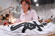 4/3/09 10:47:12 AM -- Easton, PA, U.S.A. -- Djoumile Pendeva, a seamstress at Majestic Athletic sews lettering on the back of a Chicago White Sox jersey April 3, 2009 in Easton, Pennsylvania. White Sox jerseys and gear have experienced a boost in sales with Obama, a White Sox fan, in the White House. -- .Photo by William Thomas Cain,  cainimages.com.