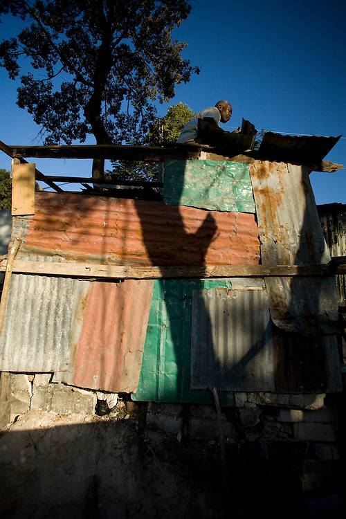 Emmanuel Michel and his son Jeff Michel build a shelter from tin and wod scraps for their family.
