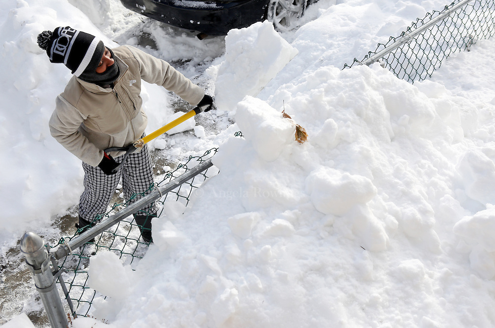 (Boston, MA - 1/28/15) Shawnda[cq] Griffin, 21, clears snow from in front of her home in Dorchester, Wednesday, January 28, 2015. Staff photo by Angela Rowlings.
