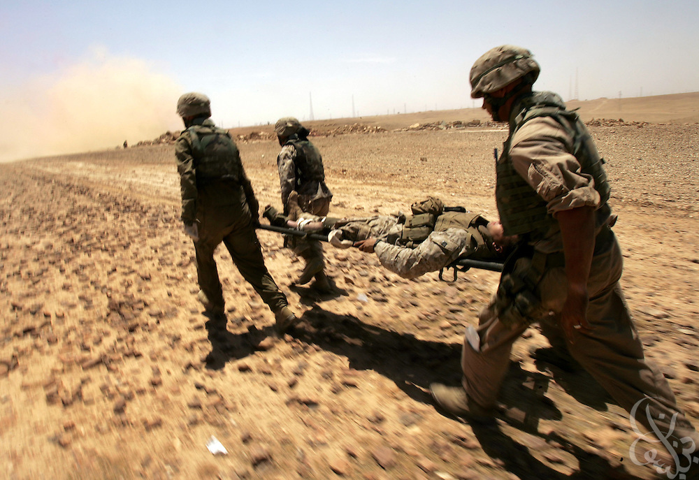 U.S. Regimental Combat Team 2 Marines med-evac a wounded Marine on a remote desert road near the Syrian border during a mission to a radio communication tower and back May 18, 2005 near the Iraqi city of Al-Qaim.