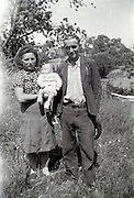 young family proud posing with their first born child countryside 1950s