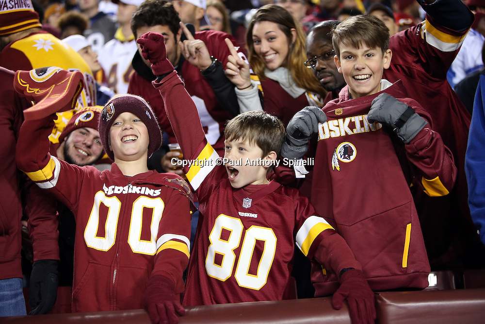 A trio of young Washington Redskins fans cheer during the Washington Redskins 2015 week 13 regular season NFL football game against the Dallas Cowboys on Monday, Dec. 7, 2015 in Landover, Md. The Cowboys won the game 19-16. (©Paul Anthony Spinelli)