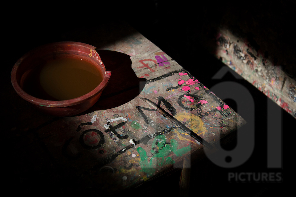 Bowl of dirty water and a paintbrush sit on a paint-stained table bathed in sunlight, Bat Trang ceramic village, Hanoi outskirts, Vietnam, Southeast Asia