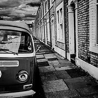 VW campervan on the street beside terraced houses