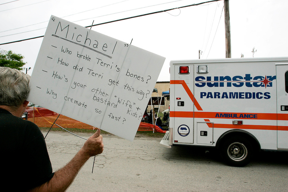 Supporters of Terri Schiavo hold up signs along the road as an ambulance drives by the Woodside Hospice on March 23, 2005 in Pinellas Park, Fla. Photo by Scott Audette/Reuters