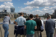 Young men stand on the Millennium Bridge to admire the views across the River Thames to the Walkie-Talkie building and Tower Bridge in City of London, on 14th May 2017, in London, England.