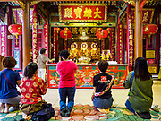 31 JULY 2018 - BANGKOK, THAILAND:  Women pray in the meditation hall at Wat Mangkon Kamalawat, the largest Mahayana Buddhist temple in Chinatown. Bangkok's Chinatown district is one of the largest Chinatowns in the world. It was established in 1781 when Siamese King Rama I gave the Chinese community in Bangkok land outside of Bangkok's city walls so he could build his palace (what is now known as the Grand Palace). Chinatown is now the heart of the Thai-Chinese community. About 14% of Thais have Chinese ancestry.   PHOTO BY JACK KURTZ