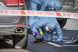 © Licensed to London News Pictures. 09/02/2019. London, UK. A police forensics officer searches beneath a vehicle at a crime scene on the junction of Lewisham Road and Blackheath Hill in southeast London where a man was shot by police. Photo credit: Rob Pinney/LNP
