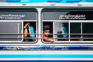 A young man peers out of a bus window, Kandy, Sri Lanka, Asia