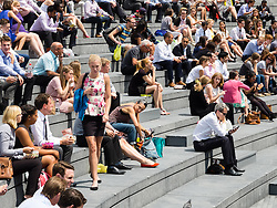 © Licensed to London News Pictures. 24/06/2014. London, UK. Office workers enjoying the hot weather in London at lunchtime today on the bank of the River Thames opposite the Tower of London. Photo credit : Vickie Flores/LNP