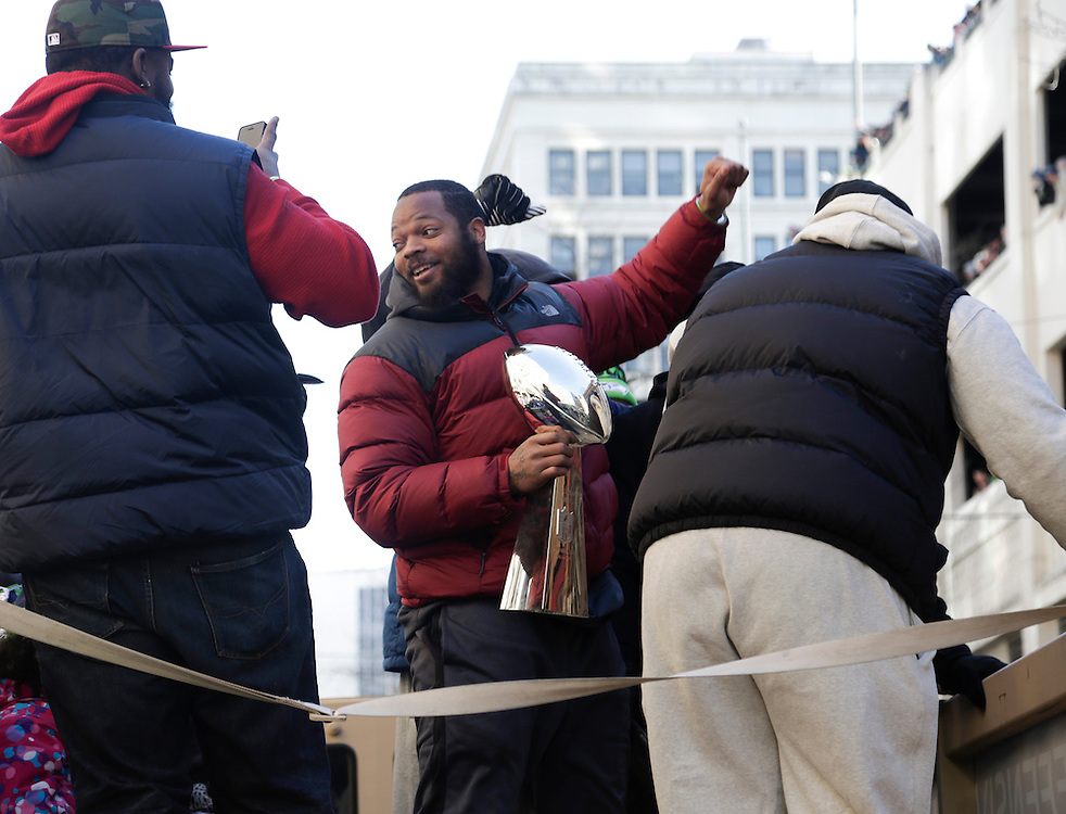Seahawks' Michael Bennett holds the Vince Lombardi Trophy during the Super Bowl victory parade for the Seattle Seahawks in Seattle, Washington February 5, 2014. Up to 500,000 Seattle Seahawks fans were expected to brave sub-freezing temperatures to celebrate the football team's first Super Bowl title at a parade set to wind through the city's downtown on Wednesday.  REUTERS/Jason Redmond  (UNITED STATES)