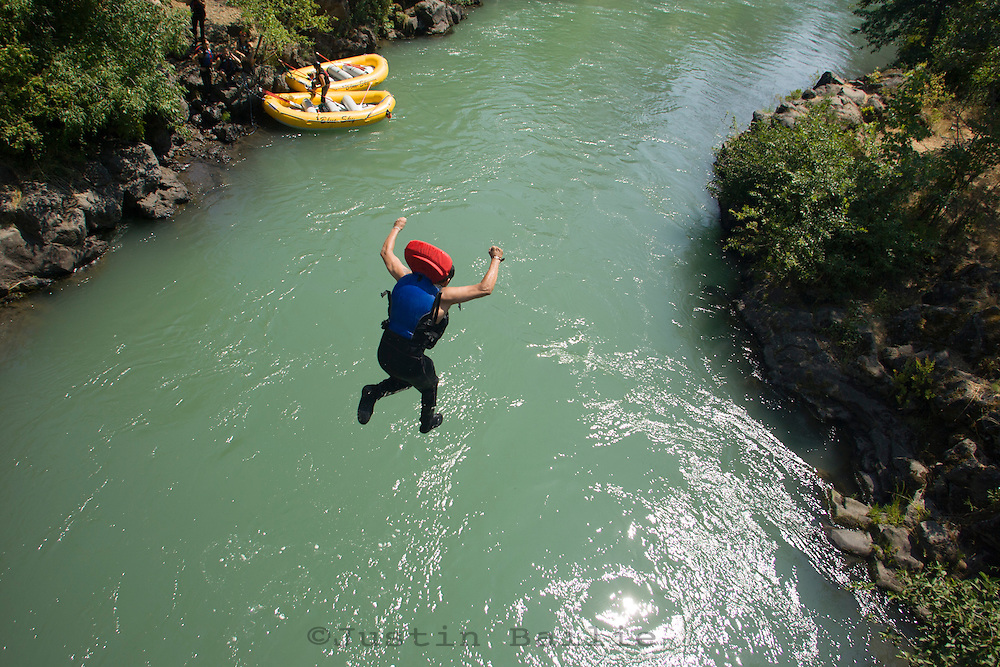 Man jumping off bridge in summer while hitewater rafting on the White Salmon River, WA.