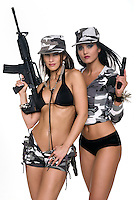 Sensual girls with powerful weapons looking at camera with military dress