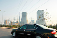New car on motorway passing Chinese industrial plant landscape coal power station near city of Jinan, Shandong Province, China