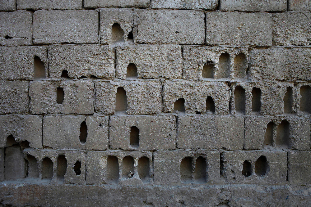 A yard wall in Koreen sprayed with holes caused by heavy fighting.<br />