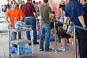 12 JUNE 2009 - SCOTTSDALE, AZ: An Apple Store employee hands out water to people waiting to get into the new Apple Store in Scottsdale, AZ. The outlet will be Arizona's largest Apple Store, occupying nearly 10,000 square feet in the Outdoor Lifestyle Center in the Scottsdale Quarter. The store, the fifth in the Phoenix area, uses a radically different design from other Apple Stores in some respects, ceilings in the building are approximately 20 feet high, and lined with a 75-foot long skylight, reducing dependence on artificial lighting. Aiding the skylight is an all-glass front and rear, permitting visitors to see directly through the store. PHOTO BY JACK KURTZ