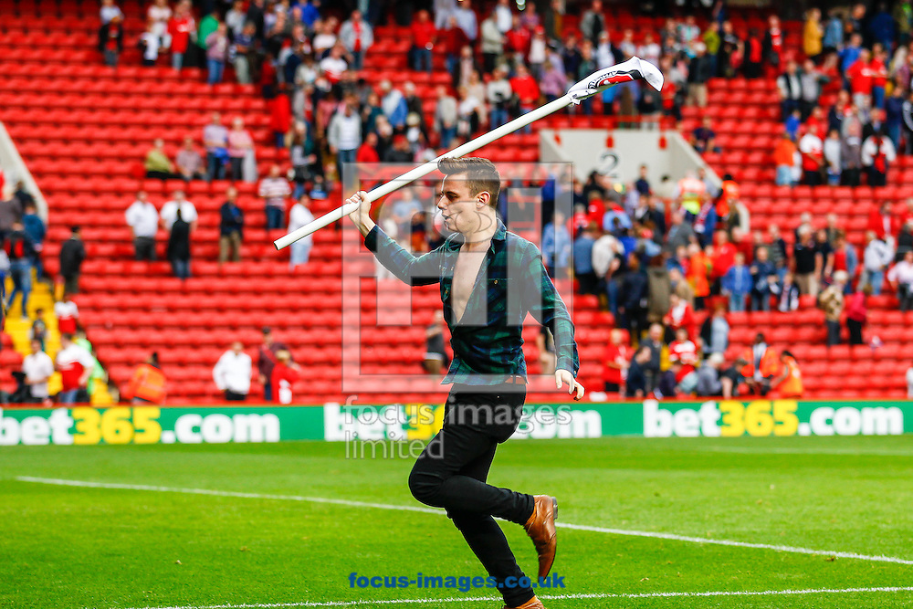 A fan enters the field holding a corner flag and runs towards the away supporters after the Sky Bet Championship match at The Valley, London<br /> Picture by David Horn/Focus Images Ltd +44 7545 970036<br /> 27/09/2014