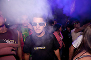 MALE CLUBBER IN SUNGLASSES LOOKING INTO CAMERA DRY ICE