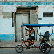 Man riding a bicycle taxi past facade of old house in Trinidad, Cuba