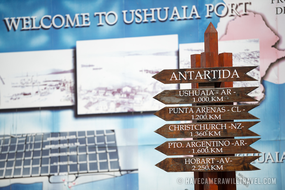 A welcome sign at Ushuaia Port, with a signpost in the foreground showing distances of outher southern cities from Antarctica. At 1,000 kilometres from Antarctica, Ushuaia is closer to the southern continent than cities such as Christchurch or Hobart.