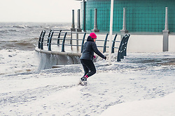 © London News Pictures. 04/01/2018. Aberystwyth, UK.  A woman gets caught by a wave the day after Storm Eleanor swept a trail of damage across the UK. Strong westerly winds gusting over 75 mph whip the high Spring Tide into huge waves that batter the seafront at Aberystwyth on the Cardigan Bay coast of west Wales. Photo credit: Keith Morris/LNP