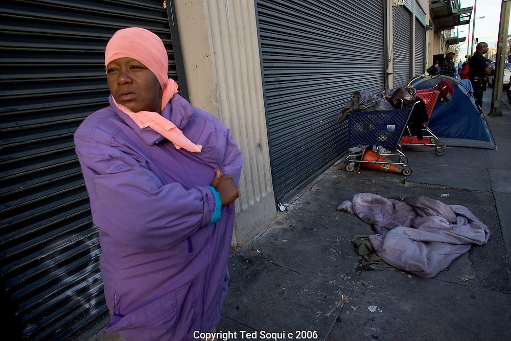 A homeless woman standing on a street in the middle of Downtown LA's skid row.