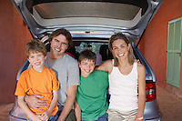 Portrait of family with two sons (6-11) sitting on car tailgate