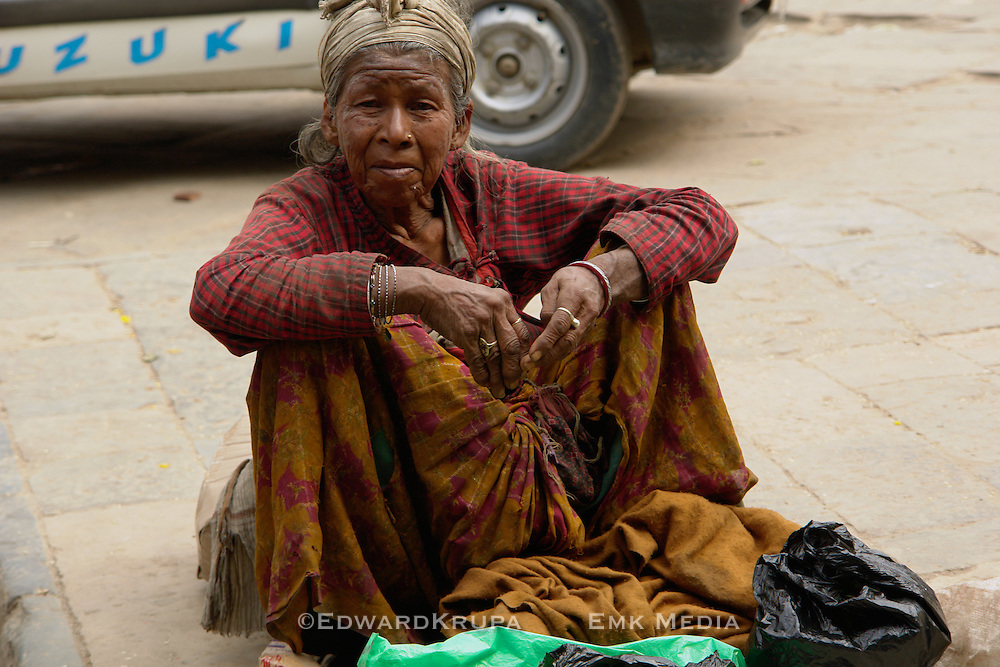 Old poor woman sitting on the street in the old market in Indra Chawk Square  of Kathmandu, Nepal.