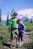 Boy, 6, and girl, 4, pause for a hug on Whistler Mountain's trail to Harmony Lake. Whistler, BC Canada.