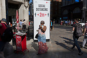 Shoppers walk past Social Distance advice at Oxford Circus on the day that UK Prime Minster, Boris Johnson announced in parliament a major easing of Coronavirus pandemic restrictions on July 4th next week, including the re-opening of pubs, restaurants, hotels and hairdressers in England, on 23rd June 2020, in London, England. The three month two metre social distance will be also reduced to one metre plus but in the last 24hrs, a further 171 have died from Covid, bringing the UK total to 42,927.