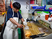 06 JUNE 2018 - SEOUL, SOUTH KOREA: A vendor slices fresh fish in the retail section of the Noryangjin Fish Market. The Noryangjin Fish Market is the largest fish market in Seoul and has been in operation since 1927. It opened in the current location in 1971 and was renovated in 2015. The market serves both retail and wholesale customers and has become a tourist attraction in recent years.      PHOTO BY JACK KURTZ