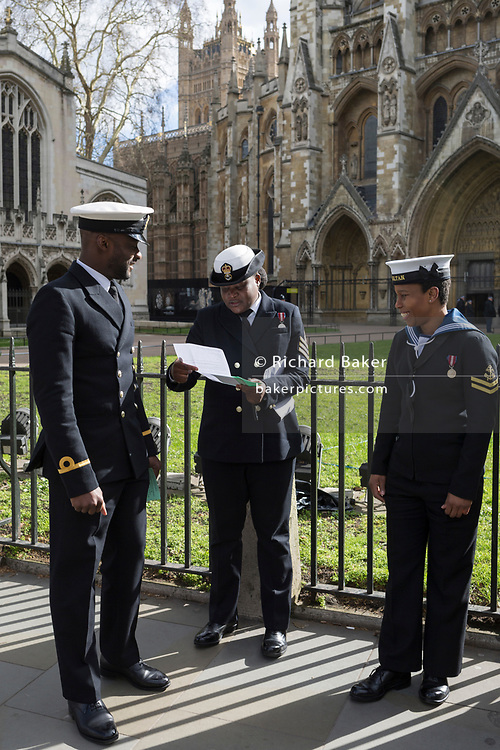 Three black Royal Navy personnel refer to instructions while waiting to enter Westminster Abbey on the occasion of Commonwealth Day, on 11th March 2019, in Westminster, London, England.