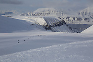 Tourists snowmobile in April down glacier above Longyearbyen; Svalbard, Norway.