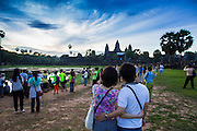 "02 JULY 2013 - ANGKOR WAT, SIEM REAP, SIEM REAP, CAMBODIA:  Tourists watch the sunrise at Angkor Wat. Angkor Wat is the largest temple complex in the world. The temple was built by the Khmer King Suryavarman II in the early 12th century in Yasodharapura (present-day Angkor), the capital of the Khmer Empire, as his state temple and eventual mausoleum. Angkor Wat was dedicated to Vishnu. It is the best-preserved temple at the site, and has remained a religious centre since its foundation – first Hindu, then Buddhist. The temple is at the top of the high classical style of Khmer architecture. It is a symbol of Cambodia, appearing on the national flag, and it is the country's prime attraction for visitors. The temple is admired for the architecture, the extensive bas-reliefs, and for the numerous devatas adorning its walls. The modern name, Angkor Wat, means ""Temple City"" or ""City of Temples"" in Khmer; Angkor, meaning ""city"" or ""capital city"", is a vernacular form of the word nokor, which comes from the Sanskrit word nagara. Wat is the Khmer word for ""temple grounds"", derived from the Pali word ""vatta."" Prior to this time the temple was known as Preah Pisnulok, after the posthumous title of its founder. It is also the name of complex of temples, which includes Bayon and Preah Khan, in the vicinity. It is by far the most visited tourist attraction in Cambodia. More than half of all tourists to Cambodia visit Angkor.         PHOTO BY JACK KURTZ"