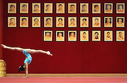 A girl on China's national gymnastics team works on her floor routine in front of portraits of former champions during training in Beijing. China has ordered its national gymnasts to turn in their computers and car keys, turn off their cell phones at 10 p.m. and stay in at night, so they will be fresh for training the next day.