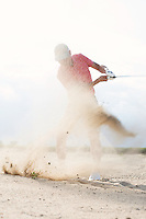 Middle-aged man splashing sand while playing at golf course
