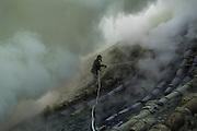 BONDOWOSO, EAST JAVA - DECEMBER 17: A sulfur miner sprays water onto sulfur pipes as he prepares the area of offfering burial during annual sacrificial ritual at Ijen crater, Bondowoso, East Java, Indonesia, December 17, 2013. The miners held the sacrifice in order to ask blessing of good result and prevent from accident or injury. The tradition begun in 1978 after a tragedy that killed four people and fourteen black out cause of poisoning gas. Daily miners produce fifteen ton of sulfur or approximately 450 ton a month. Come close to 150 miners work everyday. All the sulfur goes to sugar factory ans used as sugar whitening.