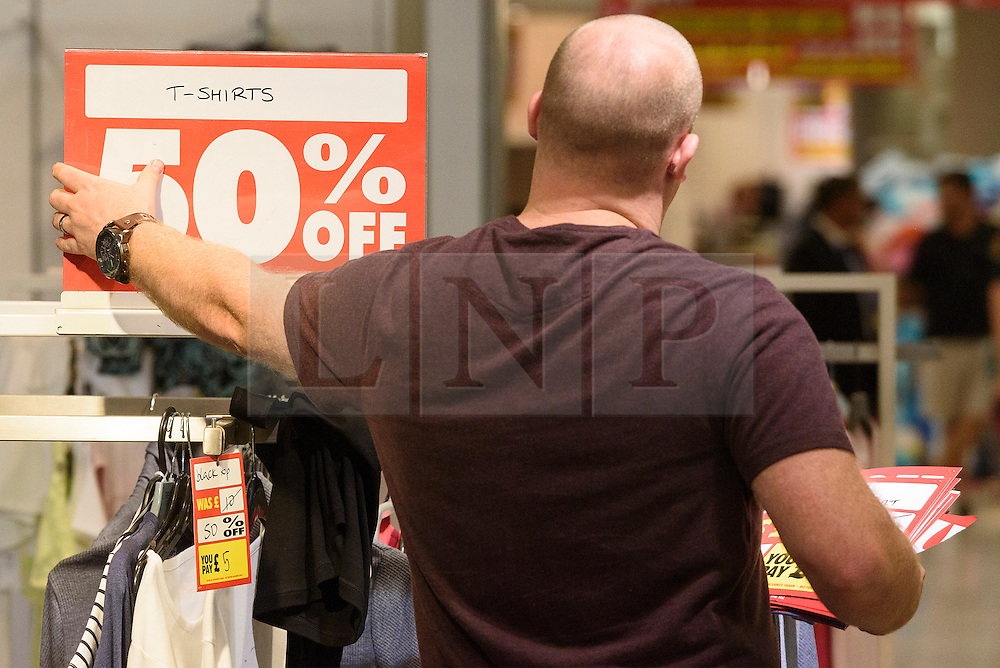 © Licensed to London News Pictures. 13/08/2016. Staff member removes discount signs as British Homes Stores Oxford Street Flagship store closes on its last day of trading. London, UK. Photo credit: Ray Tang/LNP