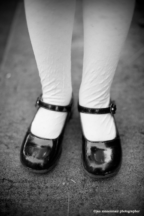 A little girl in wrinkled tights and patten leather shoes.
