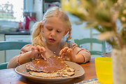 Portrait of a young girl of five eats Matzo with chocolate spread during Passover Model release available